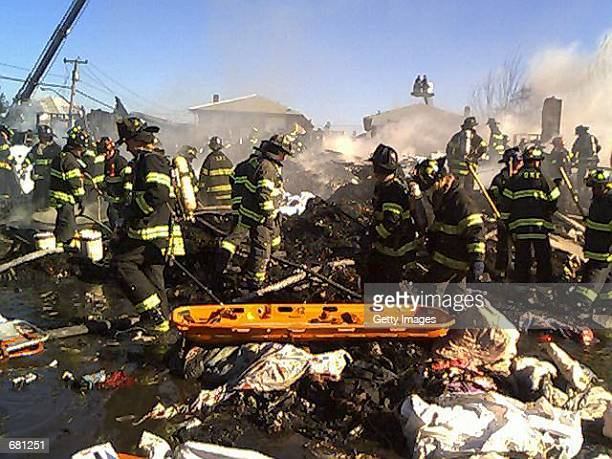 New York City firefighters remove bodies from the wreckage of American Airlines flight 587 November 12, 2001 in Rockaway Beach, Queens after the...