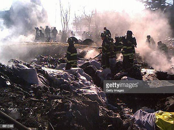 New York City firefighters sift through the wreckage of American Airlines flight 587 November 12, 2001 in Rockaway Beach, Queens after the passenger...