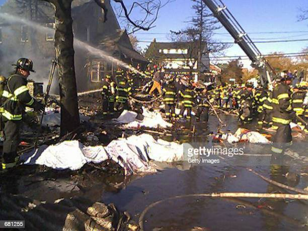 New York City firefighters sift through the wreckage of American Airlines flight 587 November 12 2001 in Rockaway Beach Queens after the passenger...