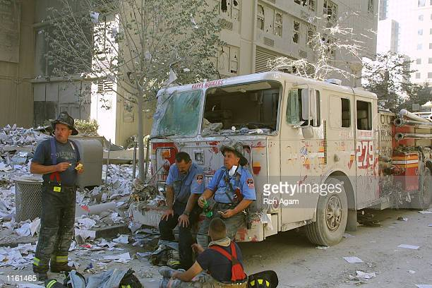 New York City firefighters take a rest at the World Trade Center after two hijacked planes crashed into the Twin Towers September 11, 2001 in New...