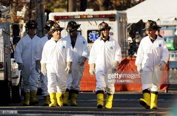 New York City firefighters wearing protective suits walk away from the scene of the 12 November crash of American Airlines Flight 587 in the Belle...