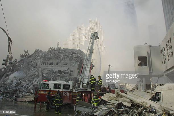 New York City firefighters work at the World Trade Center after two hijacked planes crashed into the Twin Towers September 11, 2001 in New York.