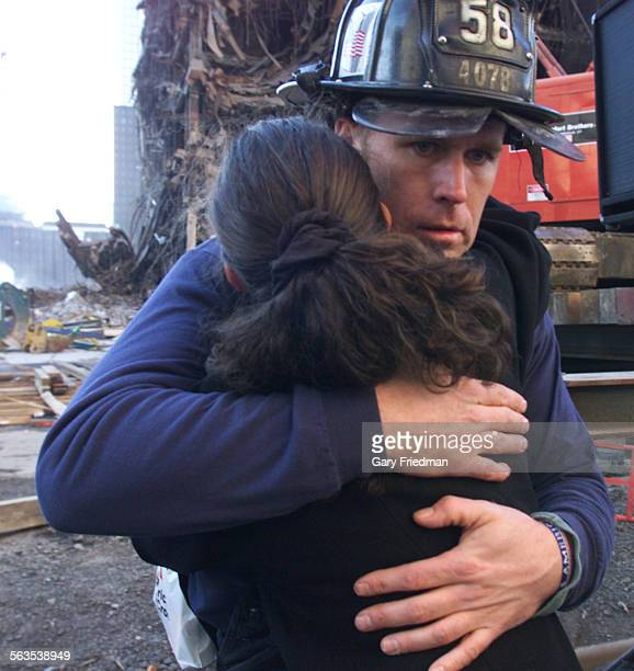 A New York City fireman Gary McNulty of engine company 58 hugs a family or friend of a victim following the Family Memorial Service held at Ground...