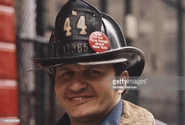 A New York City fireman wearing a badge which reads 'One of the nice things about New York' February 1976