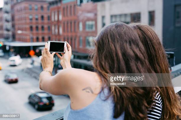 USA, New York City, friends taking a selfie with cell phone