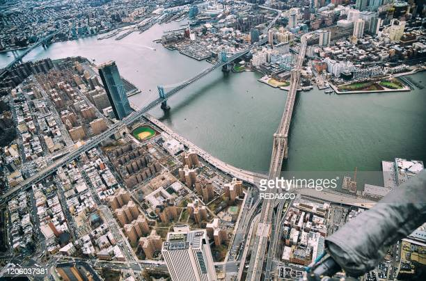 New York City from helicopter point of view. Brooklyn, Manhattan and Williamsburg Bridges with Manhattan skyscrapers on a cloudy day..
