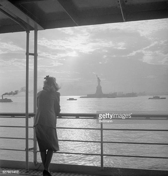 New York City Harbor- From ship deck, woman in foreground looking at a Statue of Liberty. Undated photo.