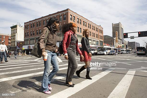 Harlem Pedestrians on crosswalk at West 125th St Frederick Douglass Blvd Famous Apollo Theater in the background