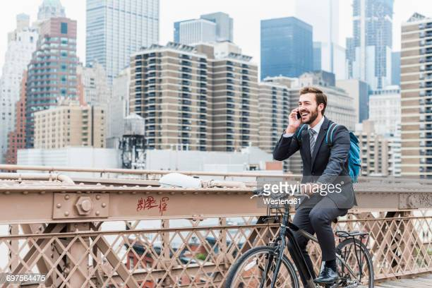 USA, New York City, laughing businessman on bicycle on Brooklyn Bridge using cell phone