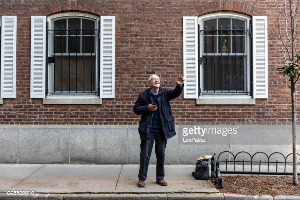 new york city life for a senior man - waving stock pictures, royalty-free photos & images