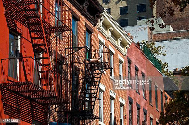 new york city life scene, young woman on fire escape - fort greene stock pictures, royalty-free photos & images