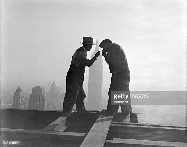 Lighting Up 'Way Up' A striking silhouette atop the gigantic RCA Building in Rockefeller Center New York as workmen light their cigarettes at the end...