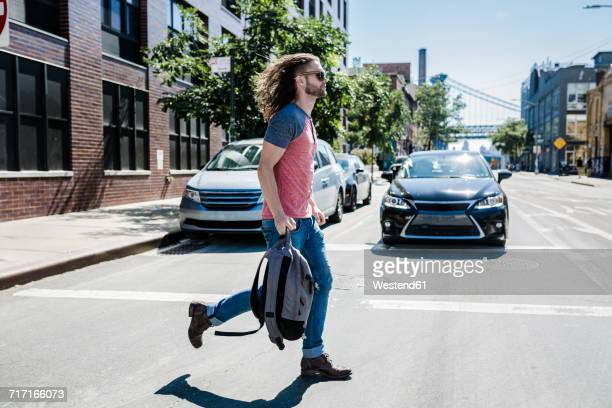 usa, new york city, man crossing the street in williamsburg, brooklyn - williamsburg new york city stock pictures, royalty-free photos & images