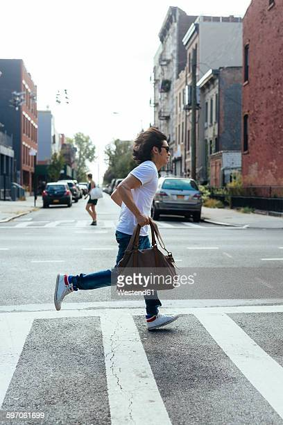 USA, New York City, man in hurry crossing the road in Brooklyn