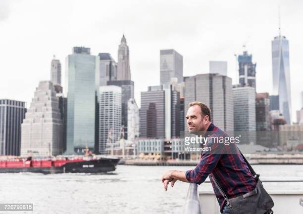 usa, new york city, man on ferry with manhattan skyline in background - ferry stock pictures, royalty-free photos & images