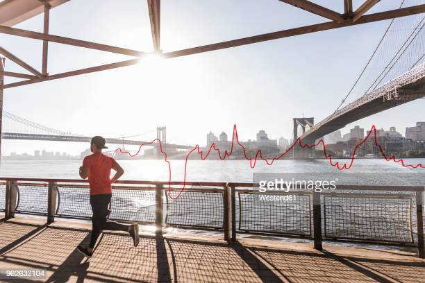 USA, New York City, man running at East River with line graph behind him