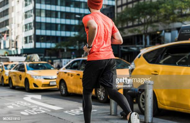 USA, New York City, man running in the city with data on pavement