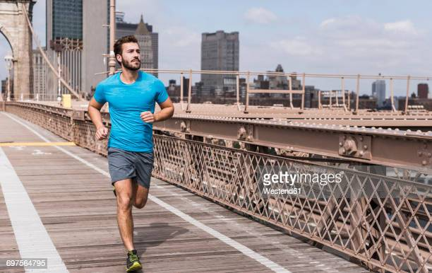 usa, new york city, man running on brooklyn brige - jogging stock photos and pictures