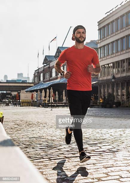 USA, New York City, man running on cobblestone pavement