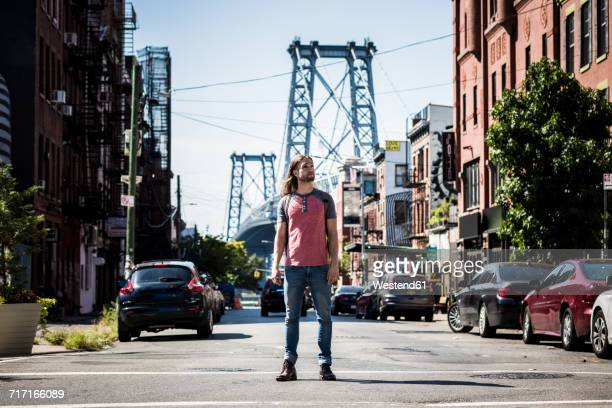 usa, new york city, man standing on the street looking around in williamsburg, brooklyn - williamsburg new york city stock pictures, royalty-free photos & images