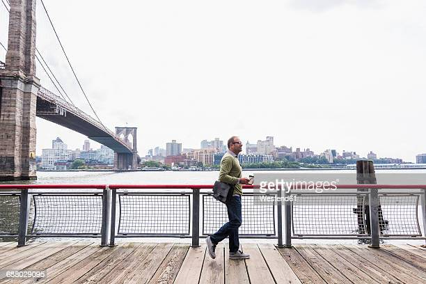 USA, New York City, man walking at East River