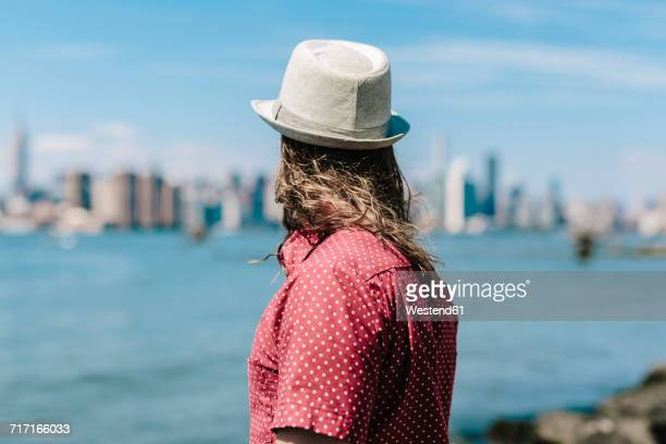 USA, New York City, man wearing hat at the waterfront looking at Manhattan skyline