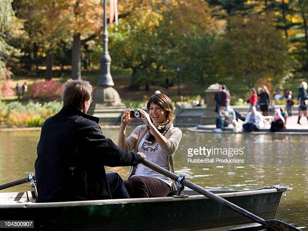 USA, New York City, Manhattan, Central Park, Mature woman photographing man in boat in Central Park