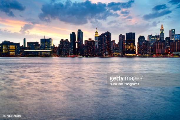 new york city manhattan midtown panorama at dusk with skyscrapers - midtown manhattan stock pictures, royalty-free photos & images