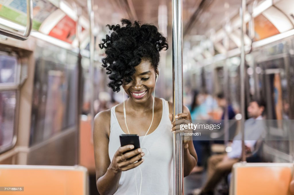 USA, New York City, Manhattan, portrait of happy woman looking at cell phone in underground train : Stock Photo
