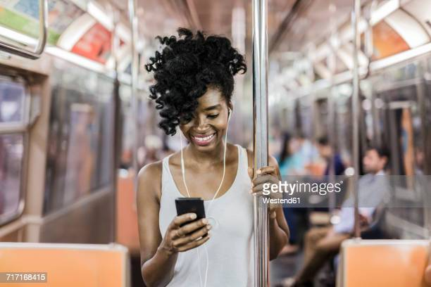 USA, New York City, Manhattan, portrait of happy woman looking at cell phone in underground train
