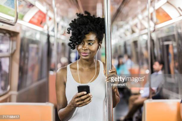 usa, new york city, manhattan, portrait of relaxed woman with cell phone in underground train - 地下鉄 ストックフォトと画像
