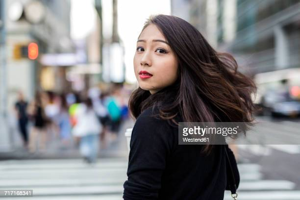 USA, New York City, Manhattan, portrait of young woman looking over her shoulder while crossing street