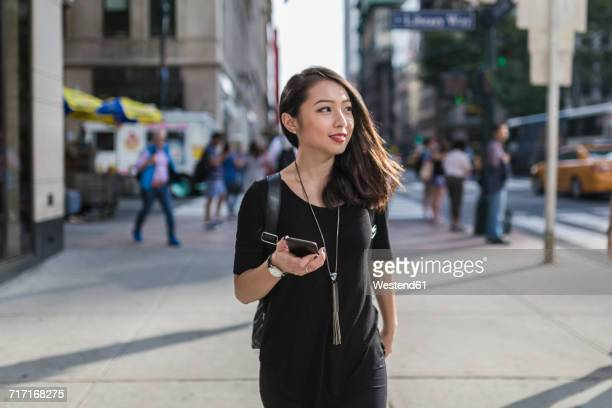usa, new york city, manhattan, portrait of young woman with cell phone dressed in black - bolsa preta - fotografias e filmes do acervo