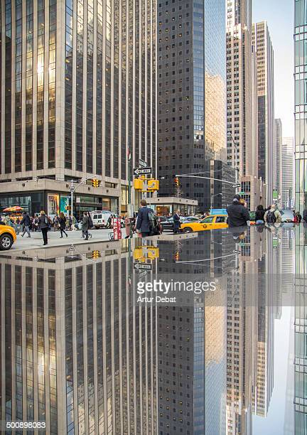 CONTENT] New York City Manhattan street life moment activity reflection ground marble towers building construction skyscraper vertical yellow taxi...