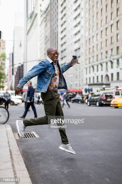 USA, New York City, Manhattan, stylish man jumping in the air