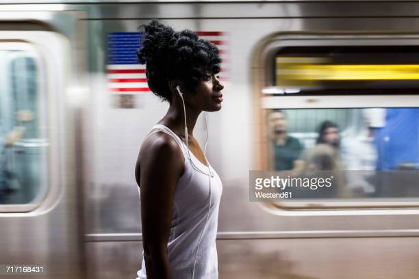 usa, new york city, manhattan, woman with earphones on subway station platform - subway platform stock pictures, royalty-free photos & images