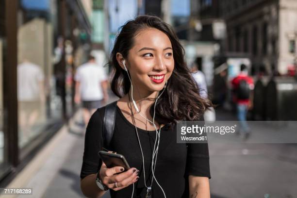 USA, New York City, Manhattan, young woman listening music with cell phone and earphones on the street