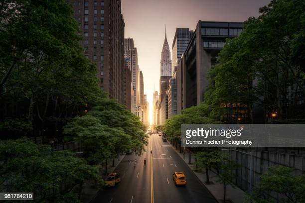new york city manhattanhenge sunset - new york city stock-fotos und bilder