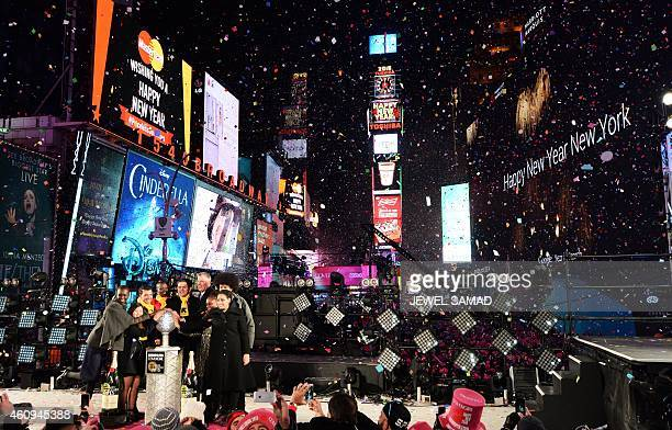 New York City Mayor Bill de Blasio along with others cheer as the ball drops at the flagpole atop of One Times Square in New York on January 1 2015...