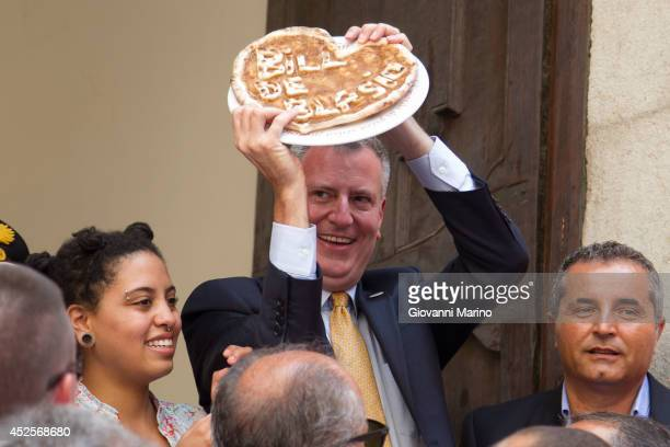 New York City mayor Bill De Blasio and his family holds a pizza with hi name on it as he visits the town his grandfather Giovanni de Blasio was born...