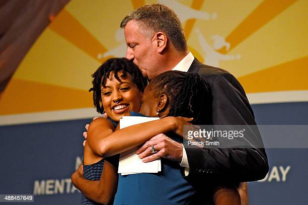New York City Mayor Bill de Blasio and his wife Chirlane McCray hug their daughter Chiara de Blasio before she received a special recognition award...