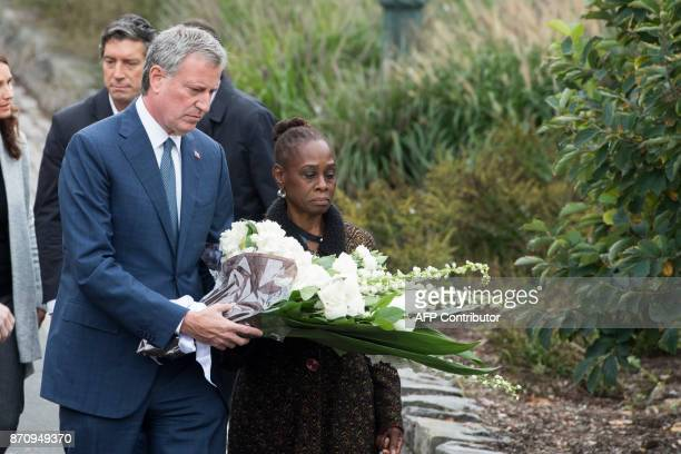 New York City Mayor Bill de Blasio and his wife Chirlane McCray lay a wreath during a ceremony on a bike path in New York on November 6 to pay...