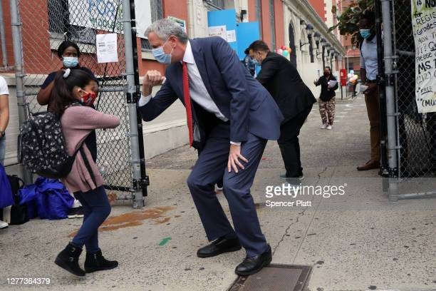 New York City Mayor Bill de Blasio elbow bumps a student at PS 188 as he welcomes elementary school students back to the city's public schools for...