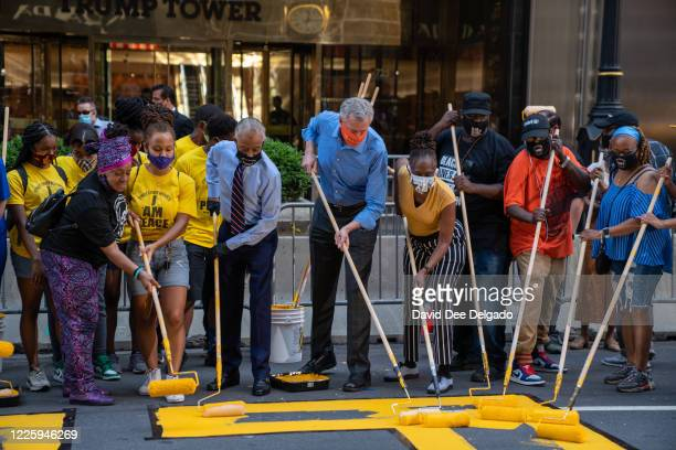 New York City Mayor Bill de Blasio his wife Chirlane McCray and Rev Al Sharpton help paint a Black Lives Matter mural on Fifth Avenue directly in...