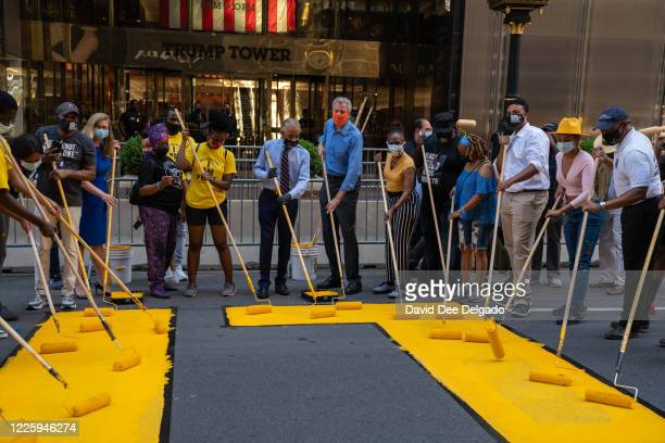 New York City Mayor Bill de Blasio, his wife Chirlane McCray and Rev. Al Sharpton help paint a Black Lives Matter mural on Fifth Avenue directly in...