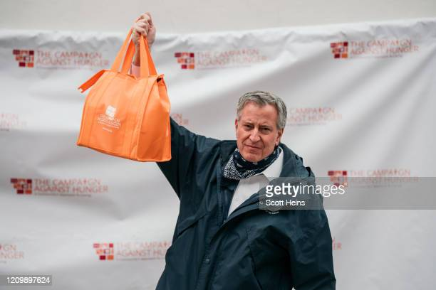 New York City Mayor Bill de Blasio holds a bag of produce packed at a food shelf organized by The Campaign Against Hunger in Bed Stuy, Brooklyn on...