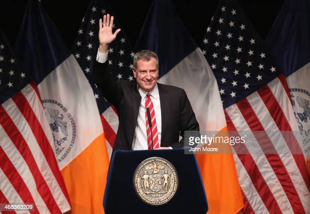New York City Mayor Bill de Blasio waves as he gives the State of the City address at La Guardia Community College on February 10 2014 in the Long...
