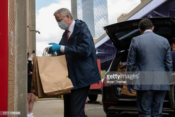 New York City Mayor Bill DeBlasio, left to right, and FDNY Commissioner Daniel A. Nigro hand out donated meals to firefighters on International...