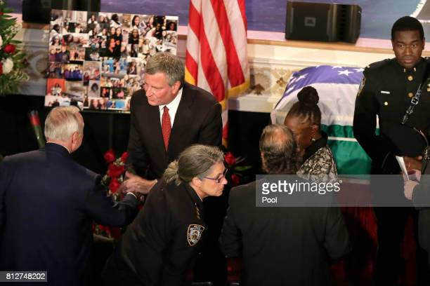New York City Mayor Bill deBlasio standing center greets former New York City Police Commissioner William Bratton as he arrives for the funeral for...