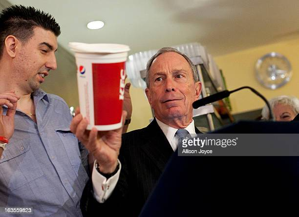 New York City Mayor Michael Bloomberg holds a large cup as he speaks to the media about the health impacts of sugar at Lucky's restaurant which...
